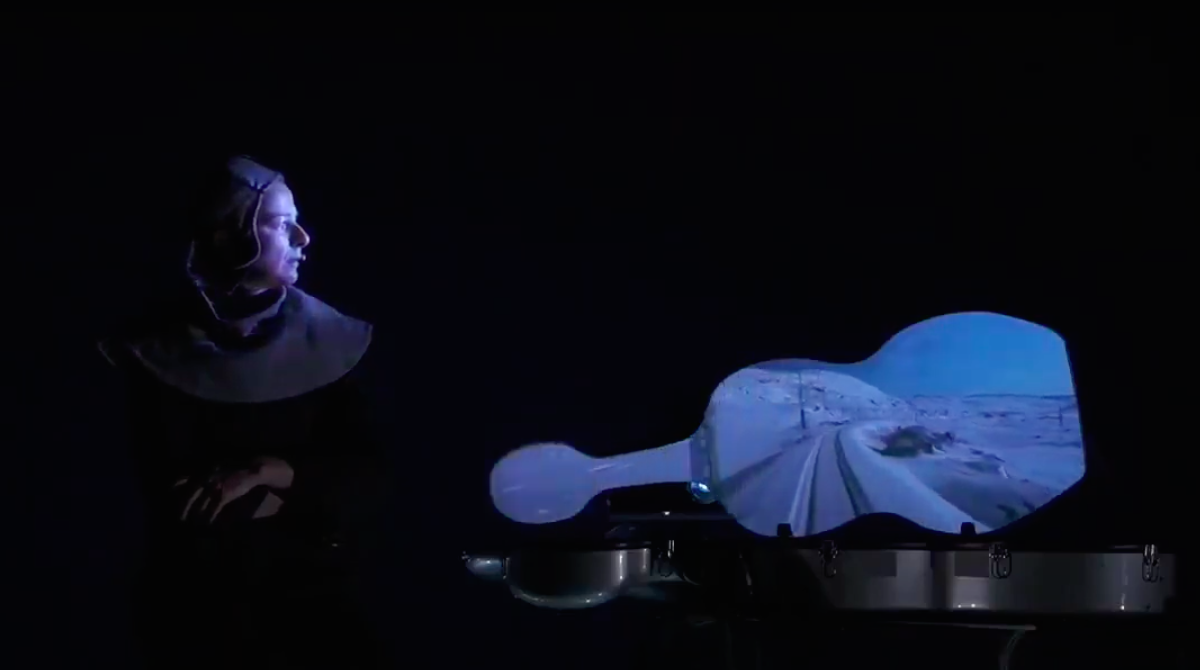 Davanti ad uno sfondo scuro, una donna è posta di profilo di fianco alla custodia aperta del suo violoncello che diventa uno schermo dal quale si vede una distesa di neve