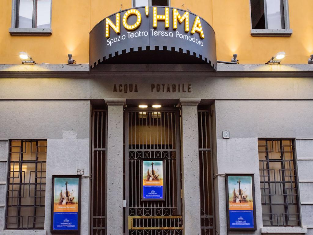 L'esterno dello Spazio Teatro No'hma di Milano dove campeggiano l'insegna, appena sotto la scritta Acqua Potabile e il cancello d'entrata -chuso- con tre locandine