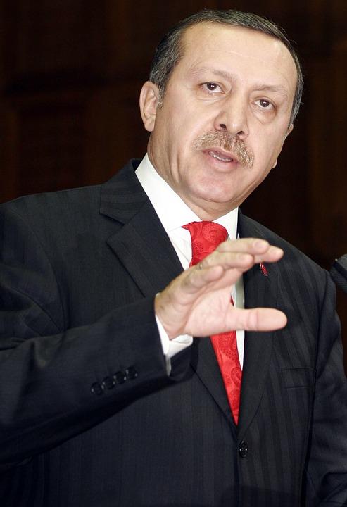 nella foto a colori si vede il Presidente della Turchia Recep Tayyip Erdoğan che indossa una giacca nera e una cravatta rossa; sta parlando a qualcuno.