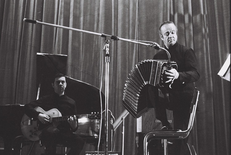 Davanti a un sipario chiuso, due uomini, uno in piedi, l'altro seduto, suonano rispettivamente una fisarmonica e una chitarra