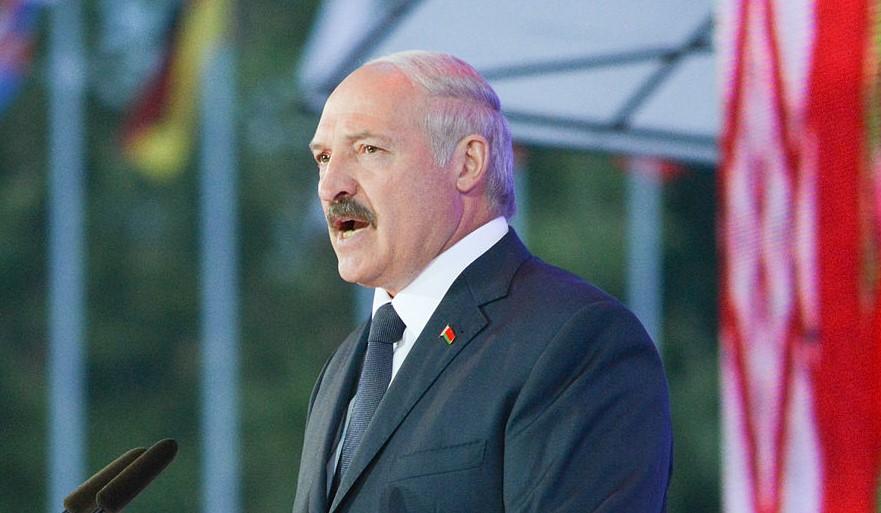 nella foto a colori si vede il dittatore bielorusso Alexander Lukashenko che tiene un discorso di fronte ad una pedana e un microfono; indossa completo scuro e cravatta scura, o blu o nero.