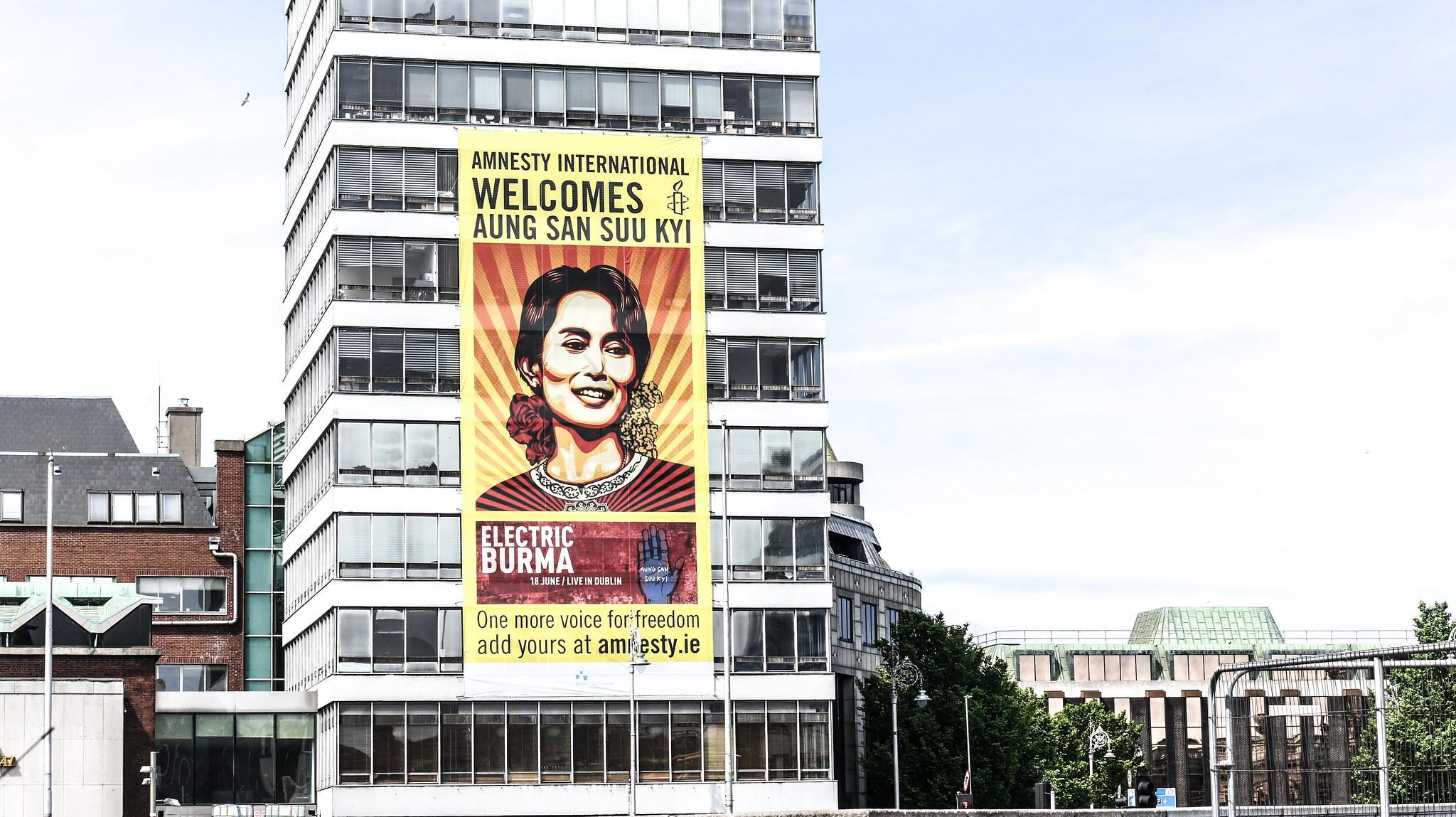 nella foto a colori si vede un edificio sul quale è stato affisso un poster di Amnesty International con l'immagine della leader Aung San Suu Kyi