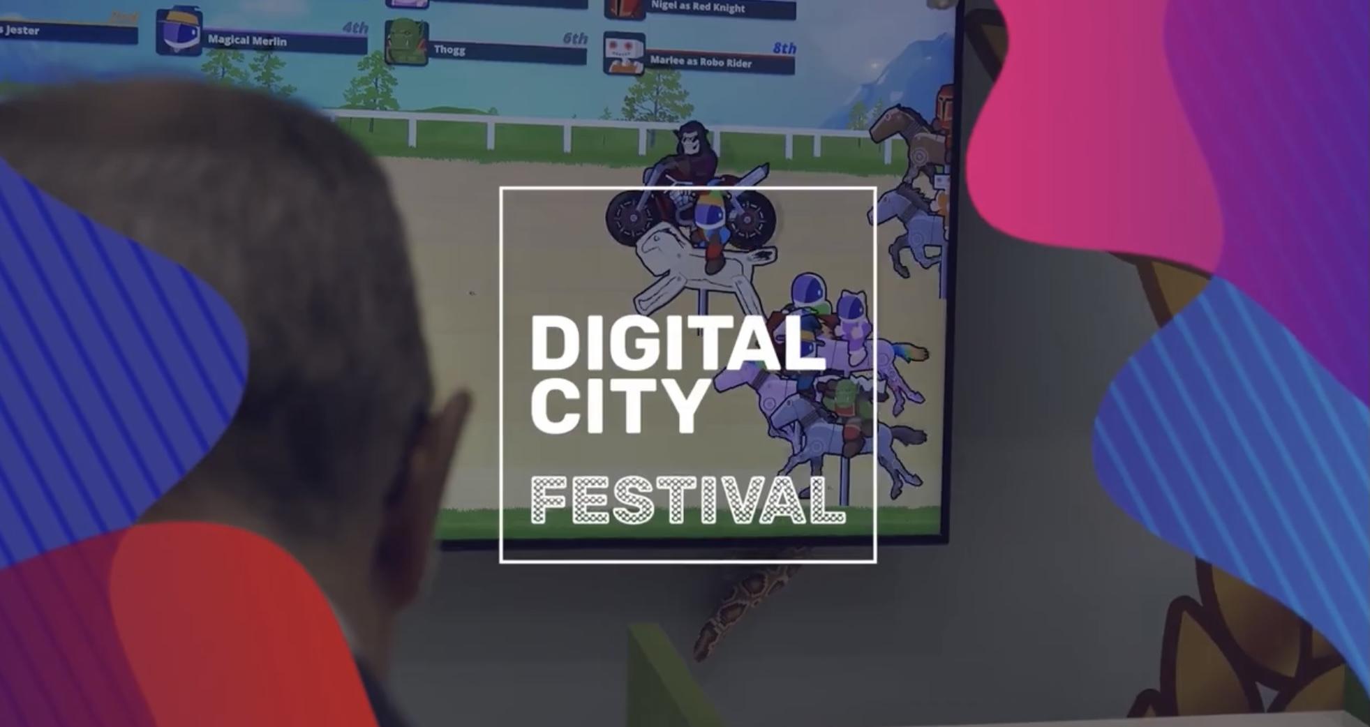 nella foto a colori si vede il logo del Digital City Festival, con questa scritta all'interno di un quadrato, e una persona che, girata di spalle, tra guardando un gioco elettronico