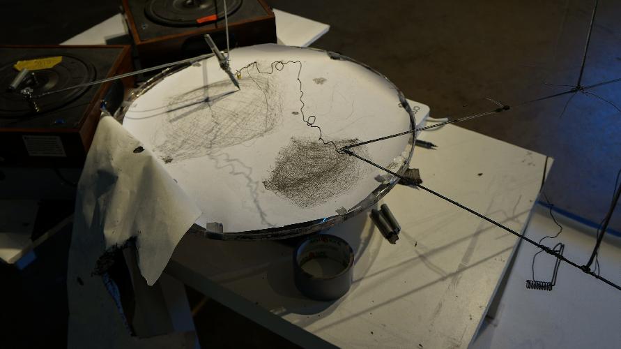 La foto mostra una delle opere meccaniche dell'artista Steven Durbach: un piatto di metallo coperto da una superficie bianca (forse carta) dove due pennini tracciano una linea continua influenzati dal movimento di un giradischi e di altri meccanismi basati sul movimento