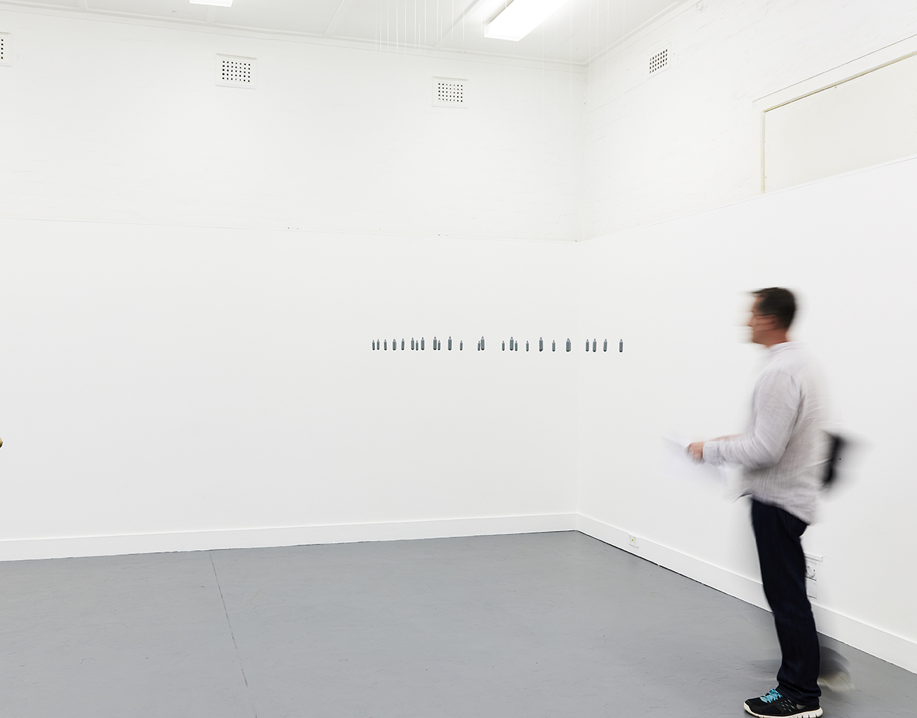 La fotografia mostra un uomo vestito con camicia bianca e pantaloni neri entrare in una stanza bianca quasi del tutto vuota all'infuori di alcuni caratteri neri che sembrano fluttuare in uno spigolo della stanza (al centro dell'immagine). La foto è leggermente mossa ed i contorni dell'uomo, nella parte destra dell'immagine sono sfumati ed indefiniti