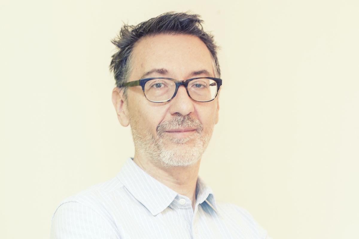 nella foto a colori si vede l'amministratore delegato di Workinvoice, Matteo Tarroni, che indossa occhaili neri e una camcia chiara a righe bianche. Ha un accenno di barba.