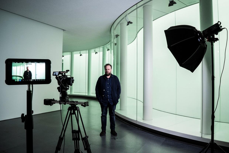 nella foto a colori si vede un signore in piedi vestito di scuro, il critico d'arte Nicolas Ballario, di fronte ad una telecamera al Museo delle Culture