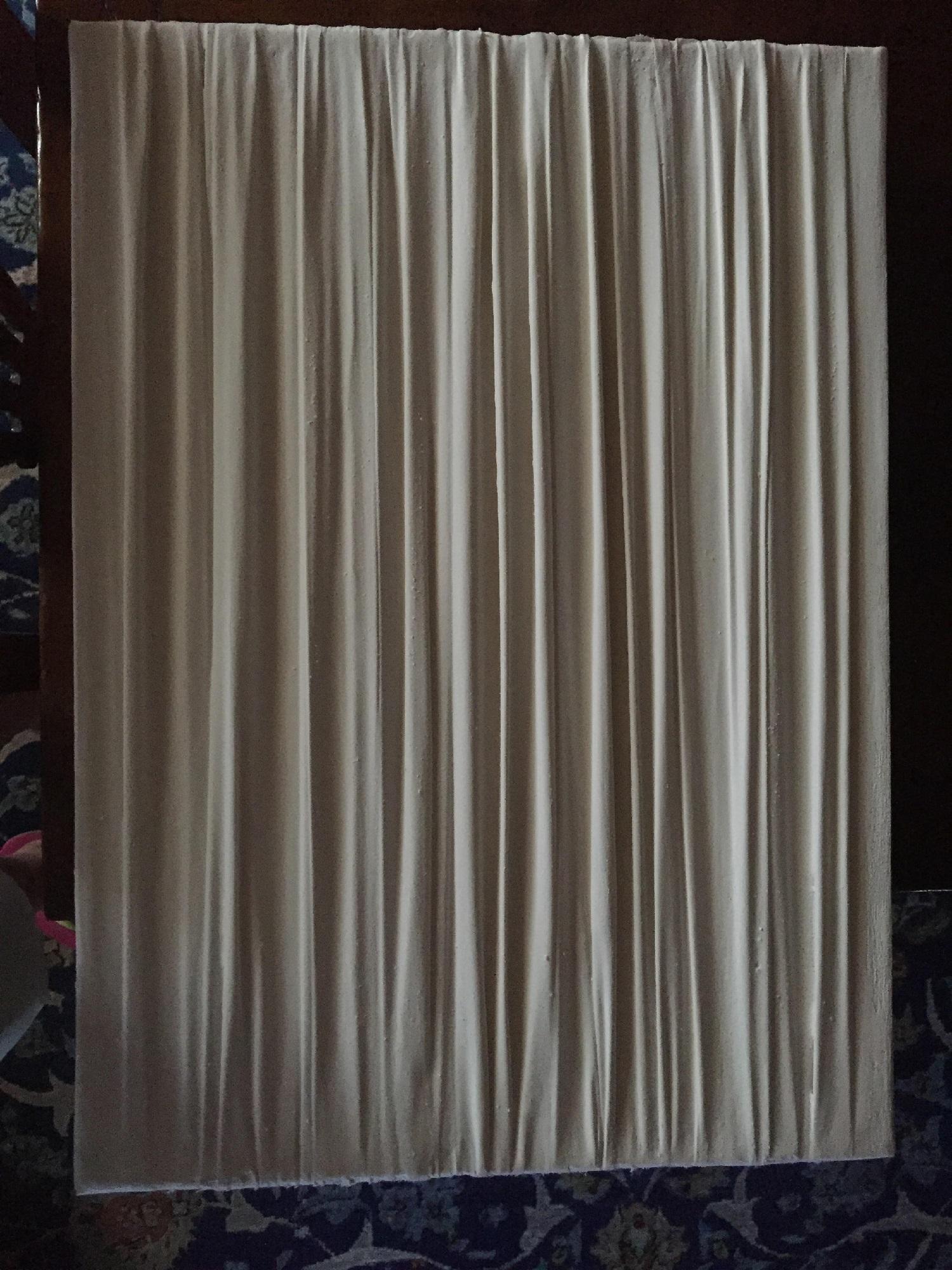 """L'opera """"Vagina monocromo"""" di Giampiero Podestà è una semplice tela bianca rettangolare ondulata, appesa su uno sfondo decorato (simile ad una carta da parati)"""