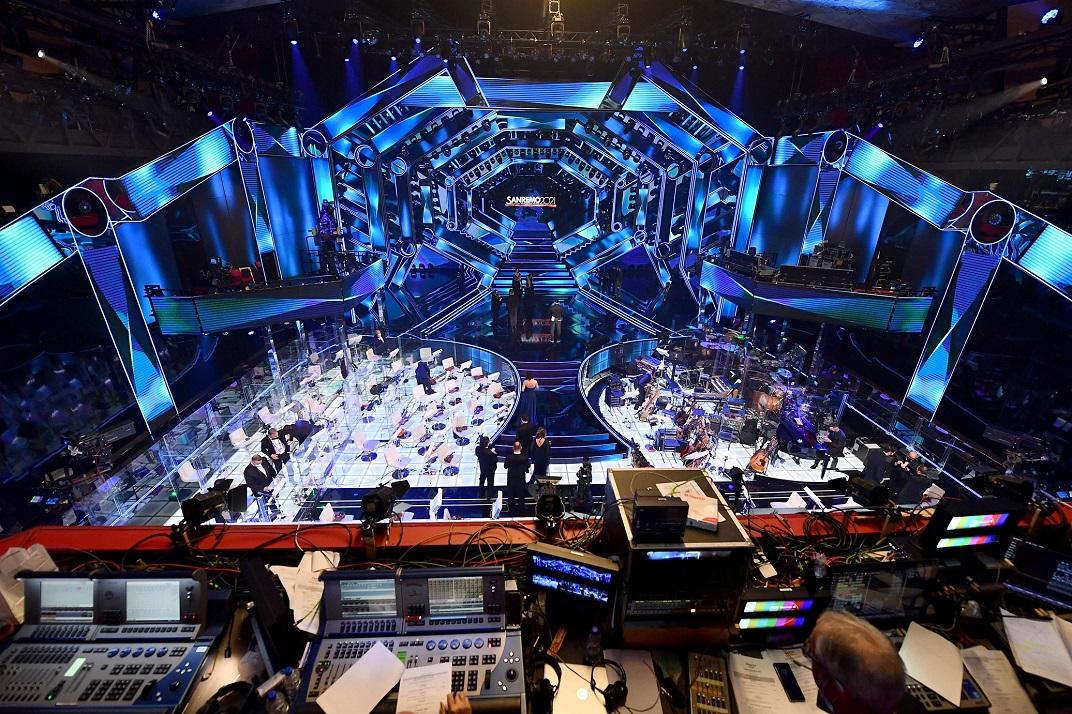 nella foto a colori si vede il palcoscenico del festival di Sanremo con luci blu e la postazione dell'orchestra ai lati dello stesso.