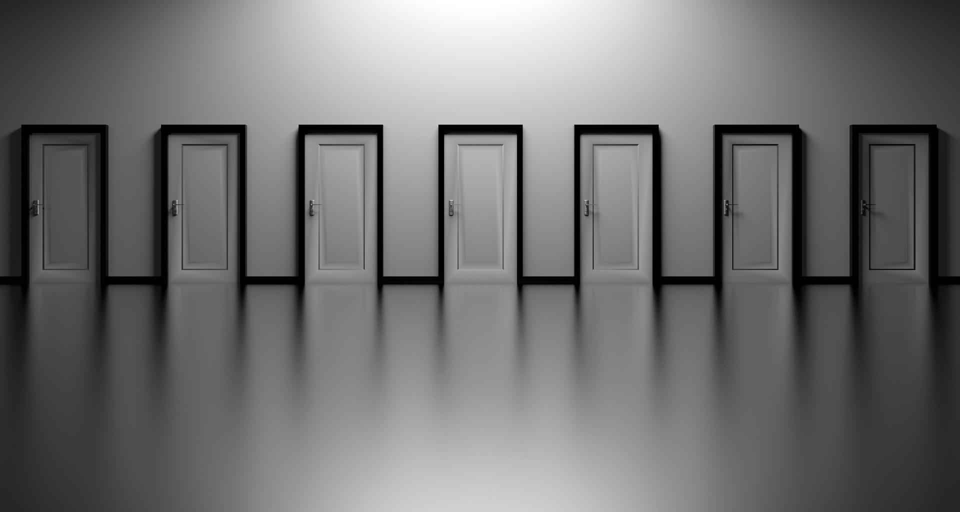 immagine in scala di grigi di una parete con 7 porte chiuse, di colore bianco