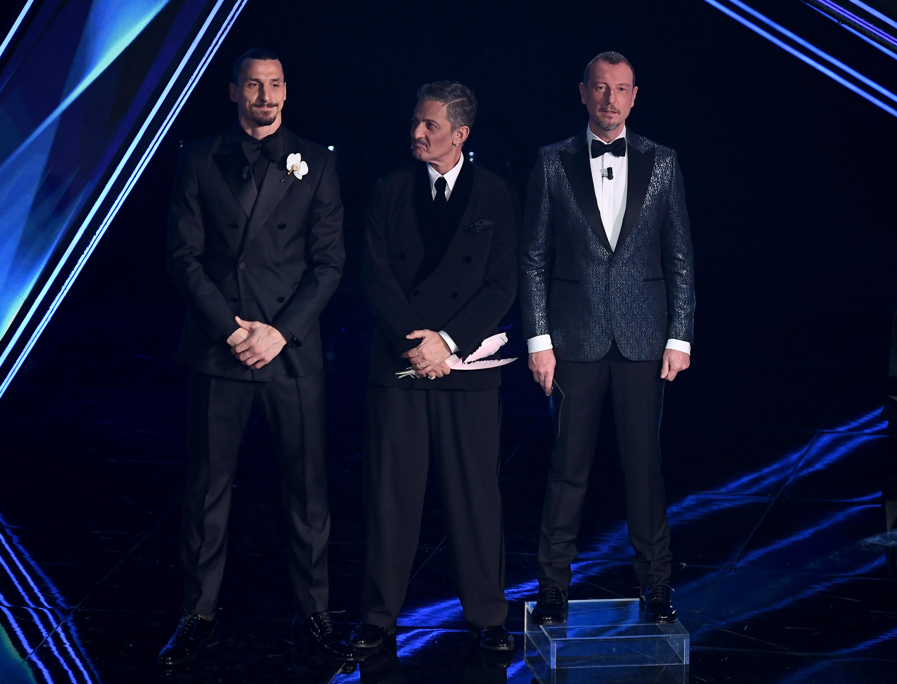 nella foto a colori si vedono, da sinistra, i tre presentatori del Festival, tutti vestiti con smoking nero escluso Amadeus, a destra, con giacca grigia che luccica.