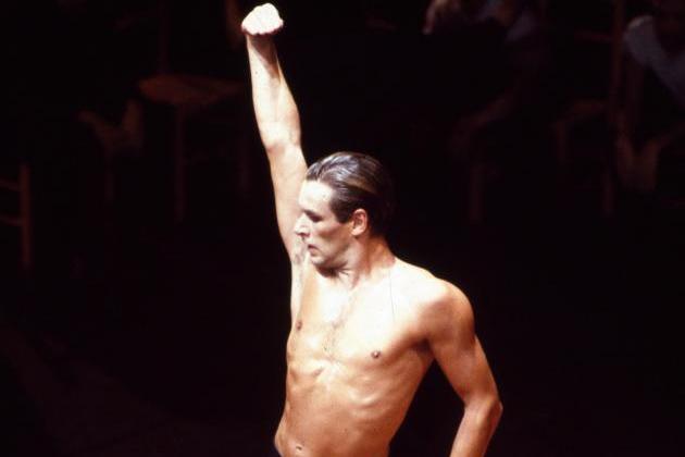 stagliata su uno sfondo scuro, una figura maschile a torso nudo tende il braccio destro verso l'altro volgendo lo sguardo verso destra