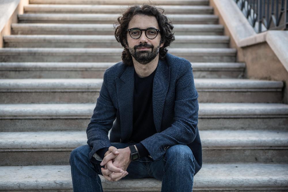 L'immagine è una foto di Andrea de Nicola, uno degli autori del libro Cosa Loro, Cosa Nostra. L'uomo ha capelli neri e lunghi, barba e occhiali. Indossa una giacca di tessuto blu, una maglietta nera e jean. L'uomo è seduto alla base di una scalinata