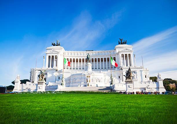 La foto mostra l'imponente complesso dell'Altare della Patria. L'edificio bianco le cui fattezze richiamo quelle di un enorme tempio antico si staglia sotto un cielo azzurro e terso, mentre sotto di esso una folla di visitatori si avvia verso l'ingresso. Il verde dell'erba occupa la parte sottostante dell'immagine
