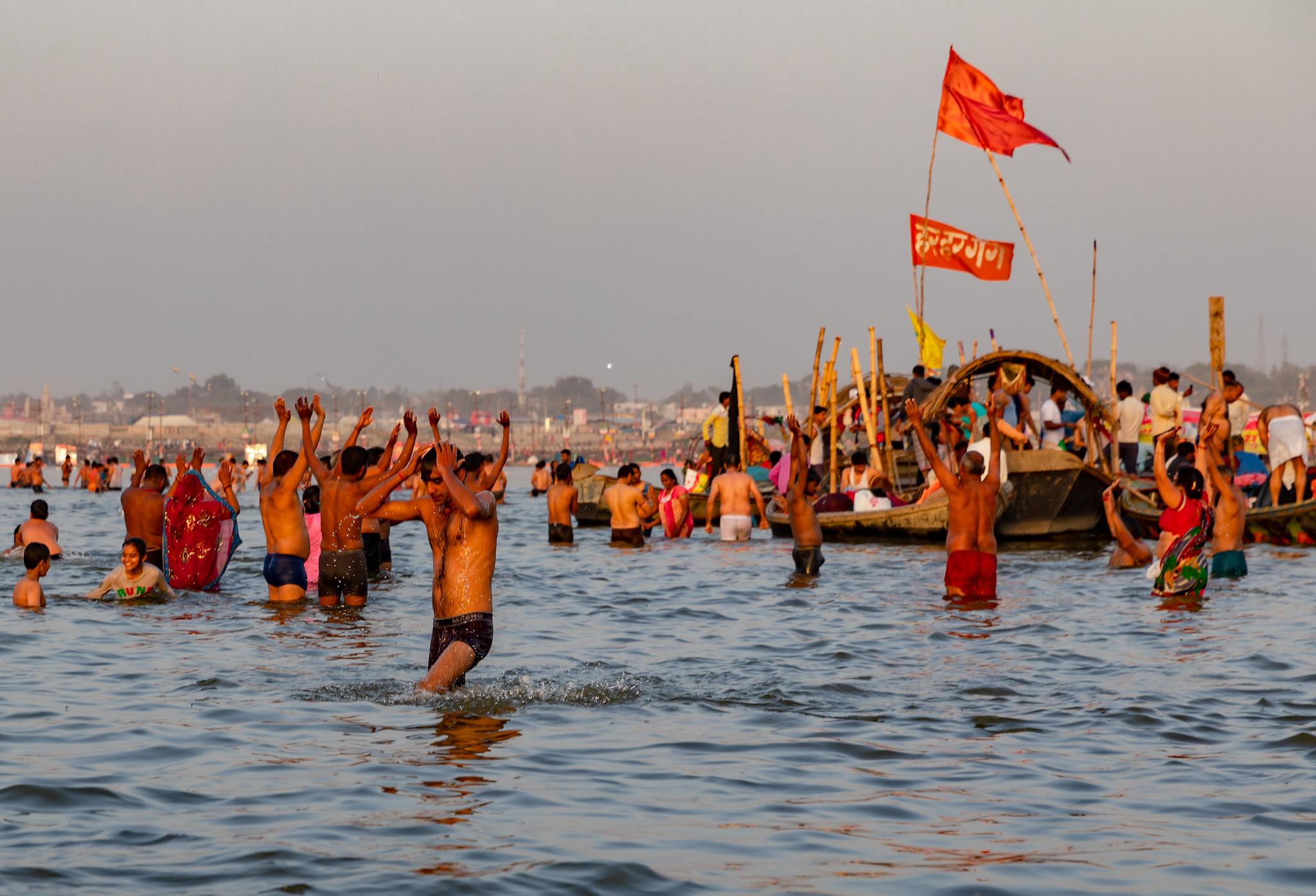 La foto mostra una folla di fedeli Indù immersi nelle acque del Gange. La maggior parte di essi, sono in acqua a torso nudo, mentre sullo sfondo, una barca stracolma di persone e con due bandiere rosse icon alcune scritte in sanscrito attraversa il fiume