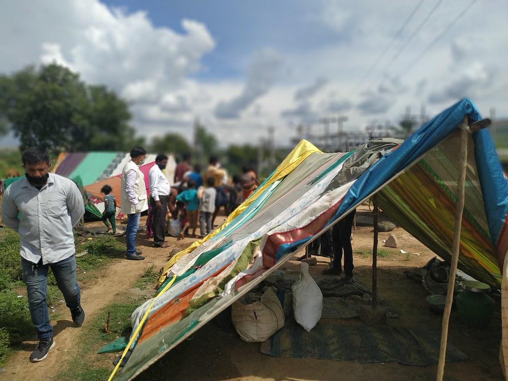 nella foto a colori si vede un campo con tende colorate, forse un campo profughi, con alcune persone di colore in piedi sulla sinistra. A destra, in primo piano, una tenda.