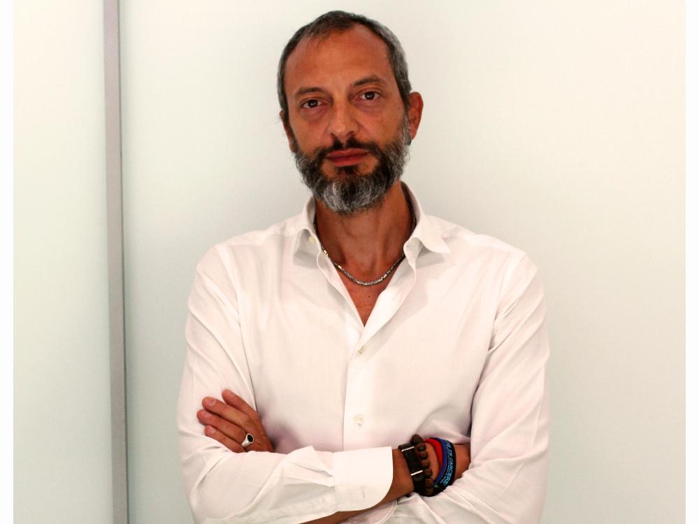 L'immagine è una foto di Giampaolo Musumeci, uno degli autori del libro Cosa Loro Cosa Nostra. L'uomo ha corti capelli e barba grigie e pelle leggermente abbronzata che contrata col bianco della camicia ed il grigio chiaro dello scorso