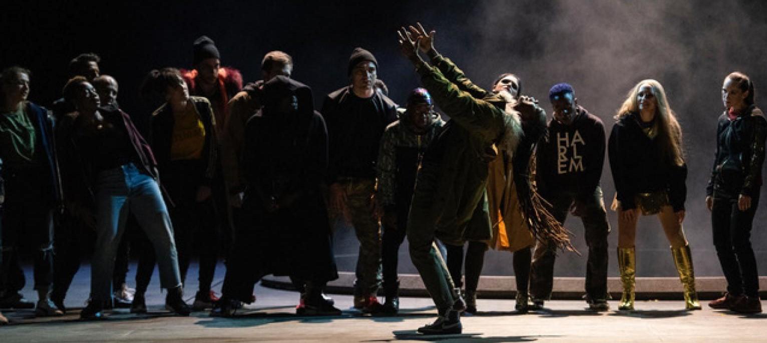 La foto mostra diversi attori esibirsi su un palco in una danza contemporanea. il cast, composto da uomini e donne di varie etnie è vestito in vario modo sebbene lo stile predominante sia casual. tra le figure spicca una donna di colore dai lunghi capelli in primo piano alzare le mani al cielo. Sullo sfondo scuro è visibile del fumo che riflette le luci di scena