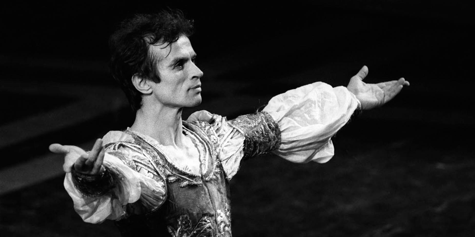 L'immagine è una foto in bianco e nero del celebre ballerino russo Rudol'd Nureev, inquadrato a bezzo busto di tre quarti, in costume e con le braccia aperte