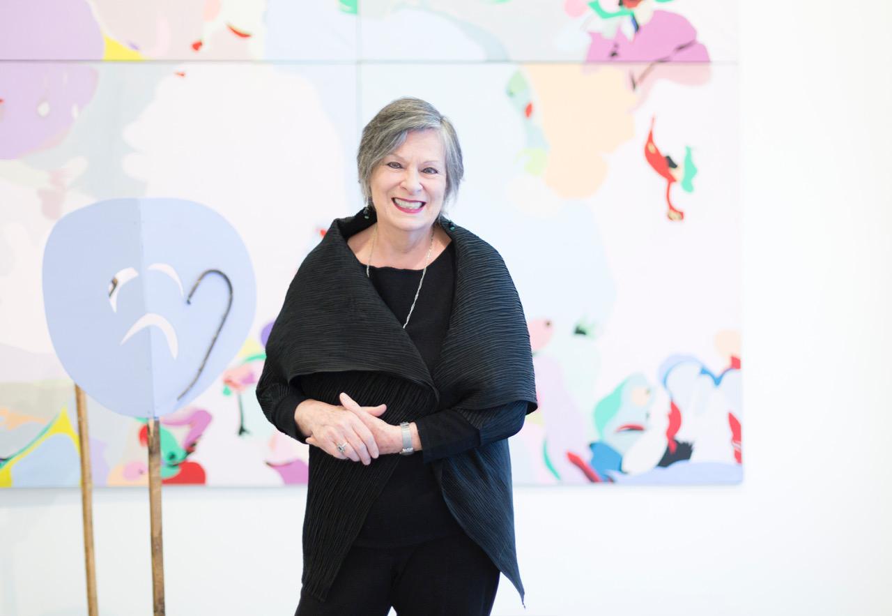 nella foto a colori si vede in primo piano l'artista e poetessa Fausta Squatriti tutta vestita di nero davanti ad un dipinto colorato. Indossa anello, orologio e collana.