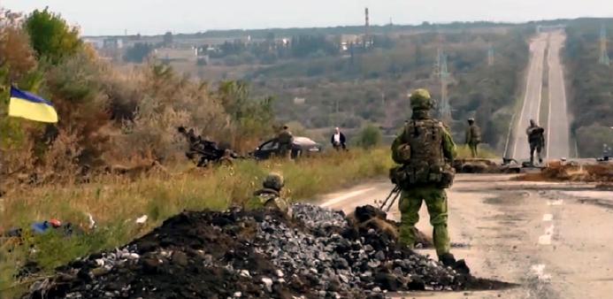 L'immagine mostra una strada nella regione ucraina del Donbass pattugliata da soldati dell'esercito nazionale di Kiev. Un soldato in primo piano è in piedi accanto ad un mucchio di pietre a bordo strada, mentre poco oltre altri soldati occupano l'area attorno ad una macchina ferma. Una bandiera ucraina è appesa ad alcuni arbusti nella parte sinistra dell'immagine