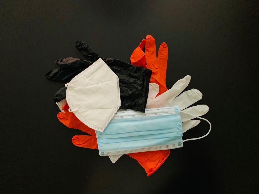 Foto di guanti in lattice bianchi, neri e mascherine protettive contro il virus Sars-CoV2