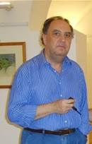 la foto a colori mostra il poeta Aldo Gerbino con in mano una pipa che indossa camicia azzurra e jeans. Ha i capelli neri e gli occhi scuri.