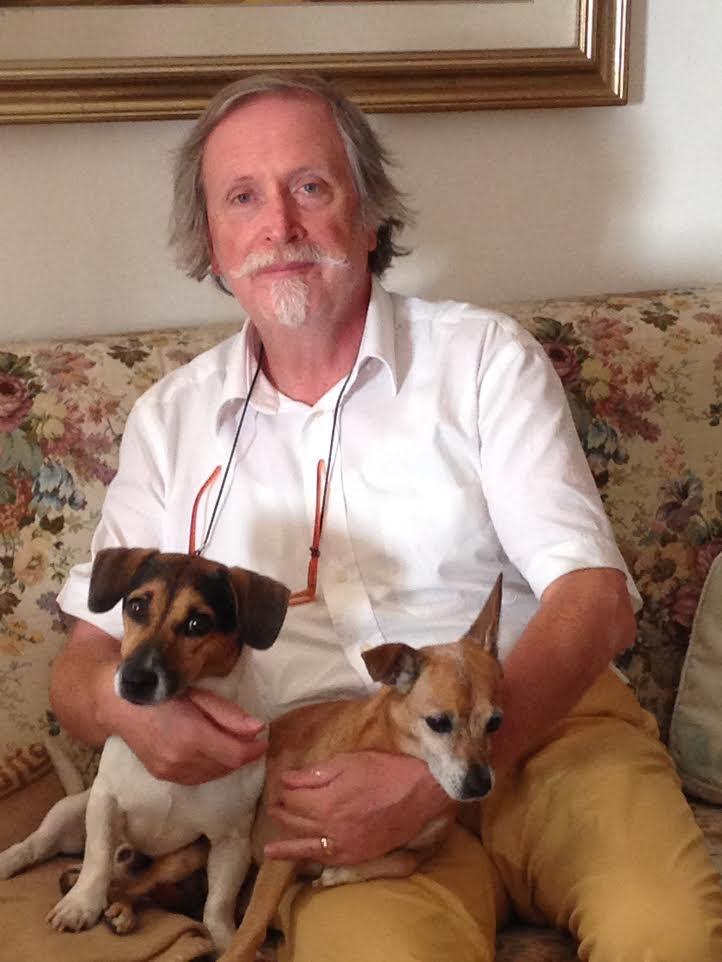 la foto a colori mostra lo scrittore Roberto Barbolini che tiene in braccio due cani; indossa una camicia bianca a maniche corte, occhiali con la catenella e pantaloni beige