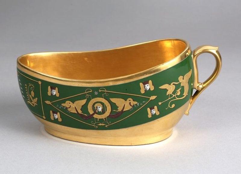 Fotografia di un vaso da notte del 1600, foglia d'oro e decorazioni figurative in verde scuro.