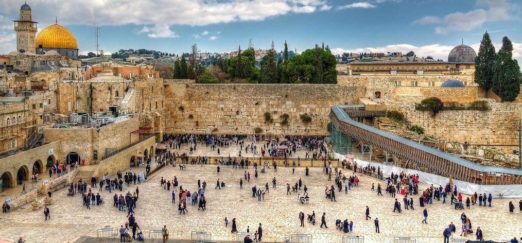 L'immagine è una foto di Gerusalemme, precisamente del Muro del pianto, ciò che resta dell'antico Tempio di Re Salomone. La piazza antistante il muro è popolata da numerosi fedeli e visitatori. Sullo sfondo si possono vedere i tetti della capitale israeliana tra cui la cupola dorata della moschea di Omar nella parte sinistra dell'immagine