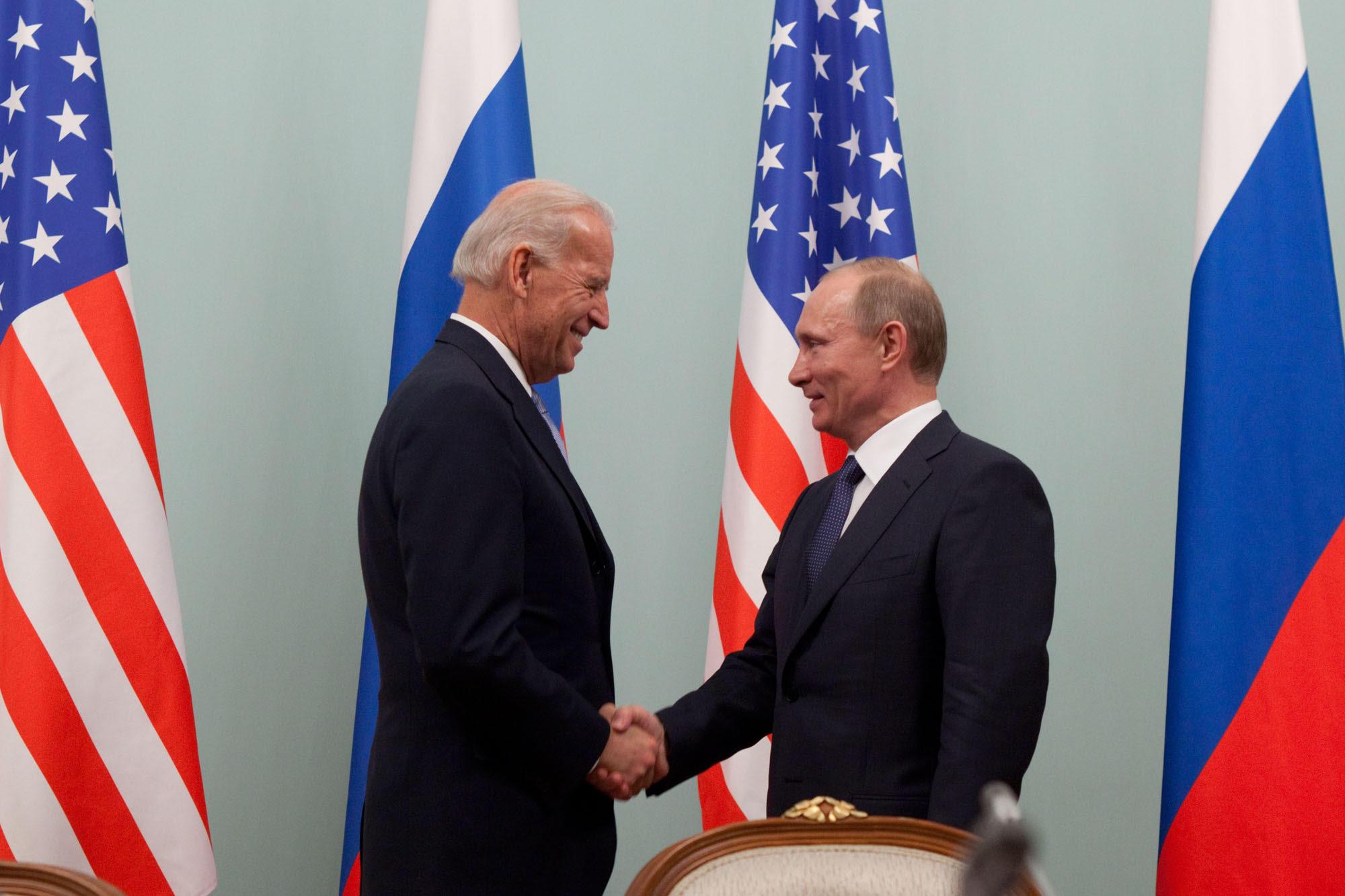 la foto a colori mostra in primo piano il Vicepresidente Usa Joe Biden che stringe la mano al Primo Ministro russo Vladimir Putin; sullo sfondo le bandiere dei due Paesi