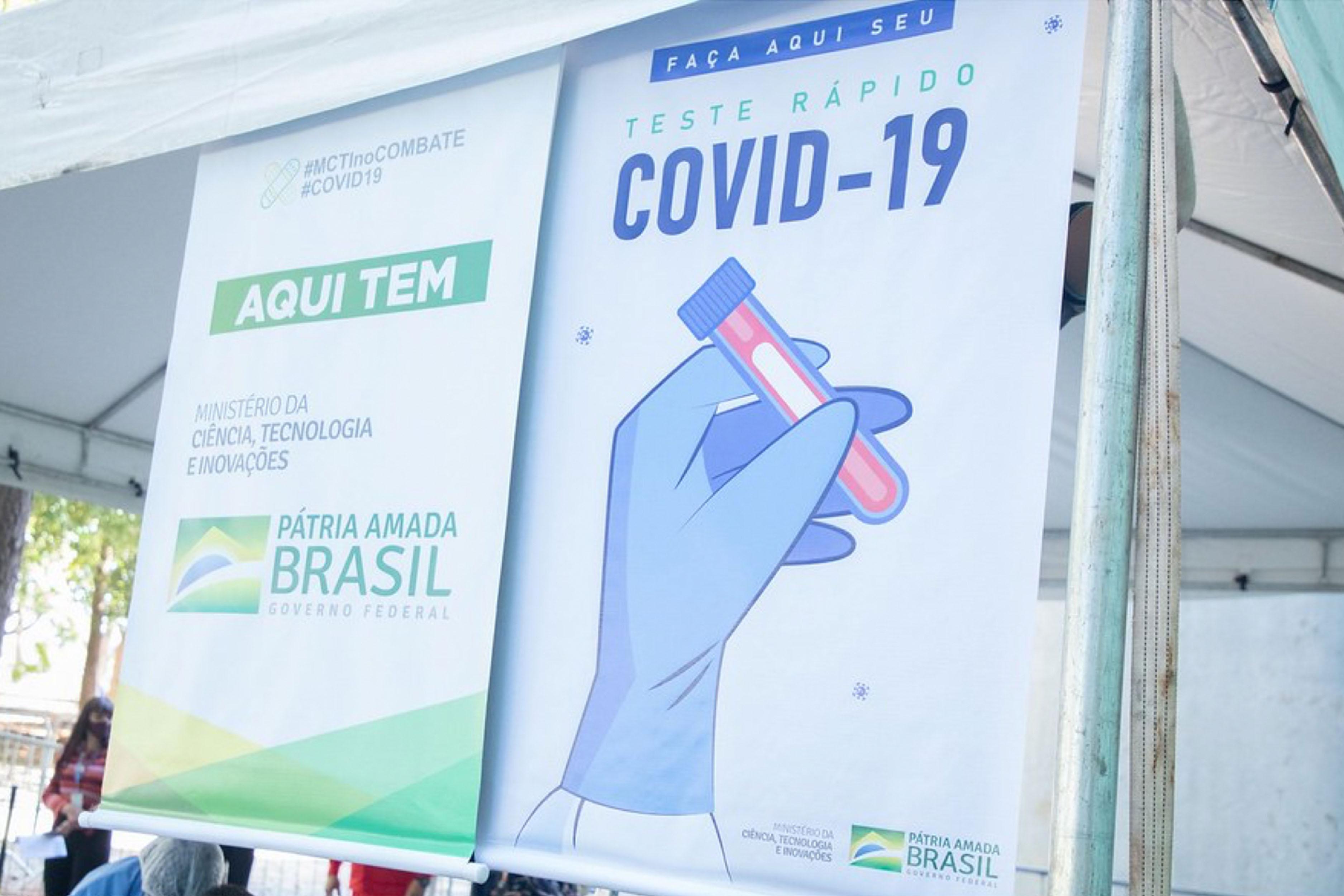 """la foto a colori mostra un poster in Brasile con la scritta """"teste rapido covid 19"""""""