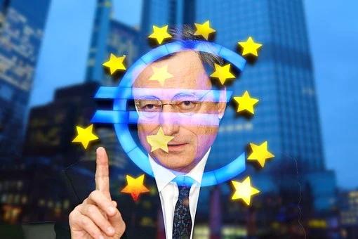 la foto a colori mostra il premier italiano Mario Draghi che indossa occhiali dalla montatura trasparente, ha il dito indice alzato della mano sinistra e il suo volto si sovrappone alle stelle dell'Unione Europea
