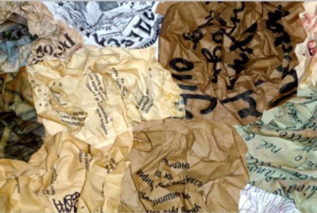 la foto a colori mostra carte di diversa tonalità di marrone, accartocciate, con scritte nere sopra