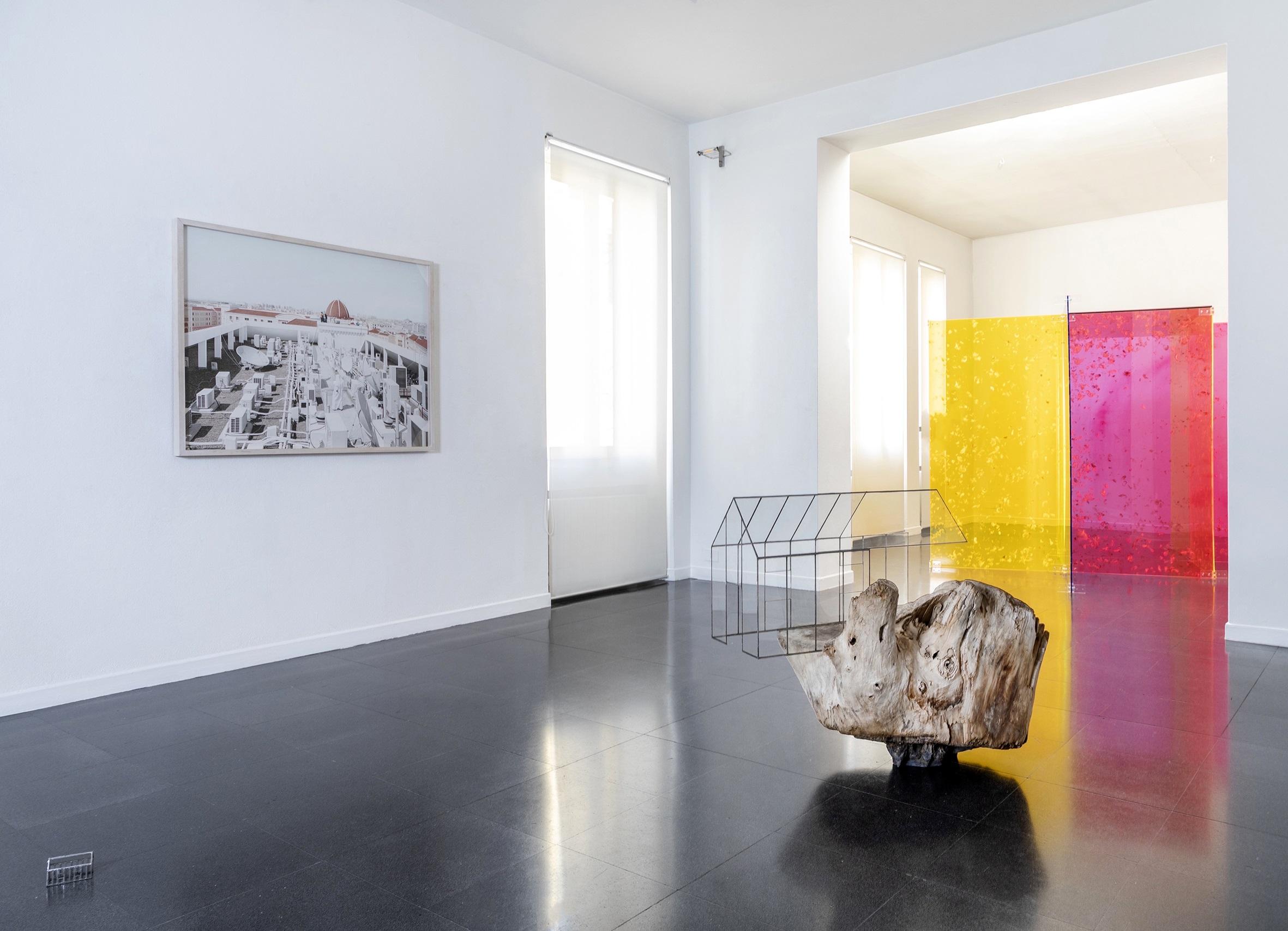 L'immagine mostra una sala bianca di una gallerie d'arte con al suo interno tre opere di tre diversi artisti (Francesco Jodice, Alfredo Pirri e Andrea Santarlasci)