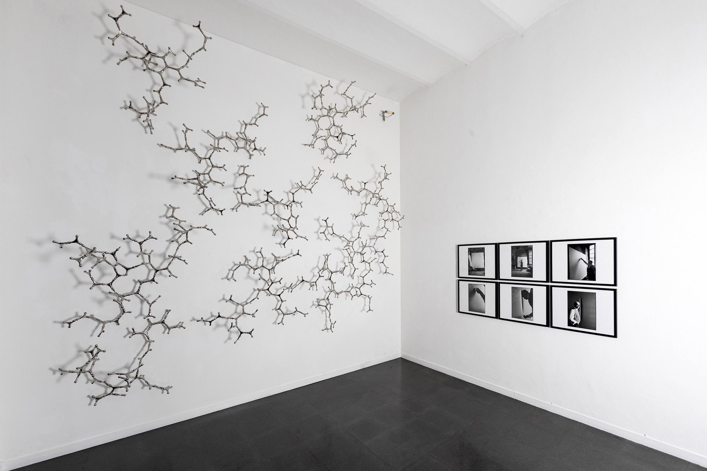 L'immagine mostra una sala bianca di una gallerie d'arte con al suo interno tre opere di tre diversi artisti (