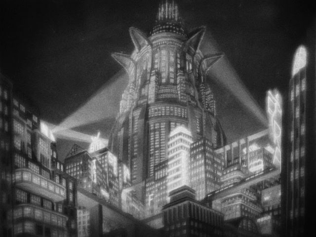 la foto in bianco e nero ritrae un edificio elevato e, intorno, altri edifici più bassi, sormontati da tre aloni luminosi