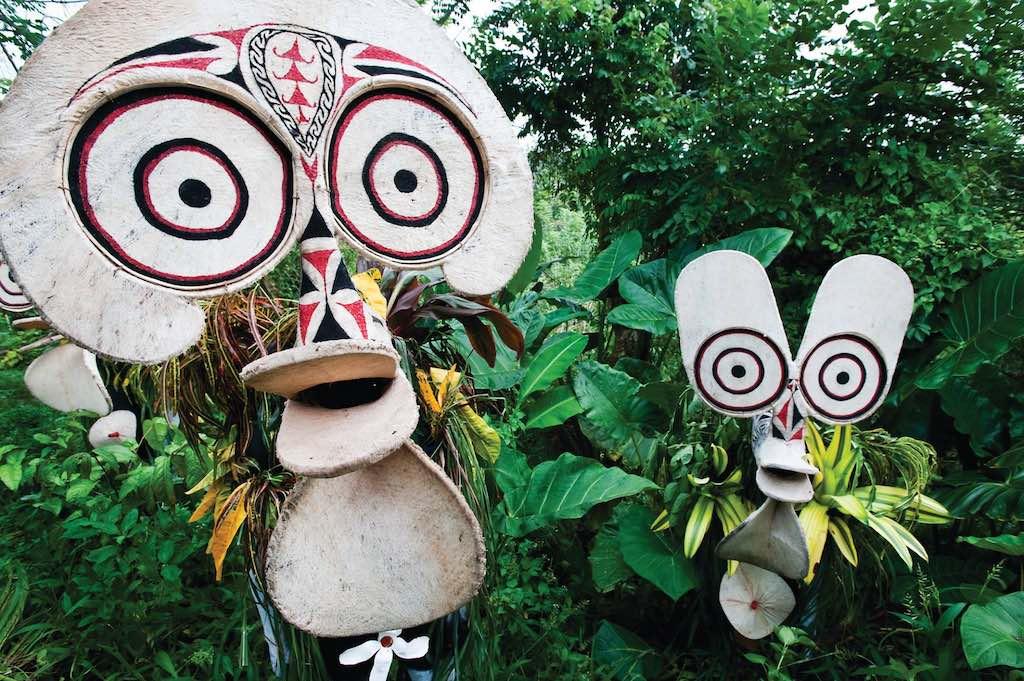 nella foto a colori si vedono due maschere bianche con dei cerchi concentrici, immersi tra il fogliame