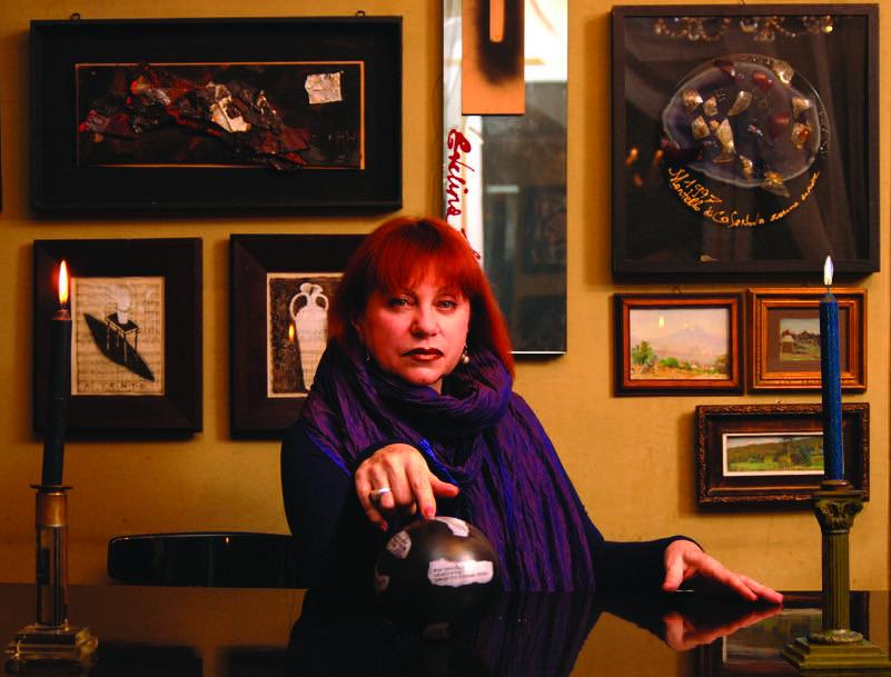 Fotografia che mostra Schatz, artista la cui patria è la Russia, seduta di fronte a un tavolo su cui vi sono due candelabri con candele accese, una mano tesa in avanti, sullo sfondo una parete con opere d'arte appese