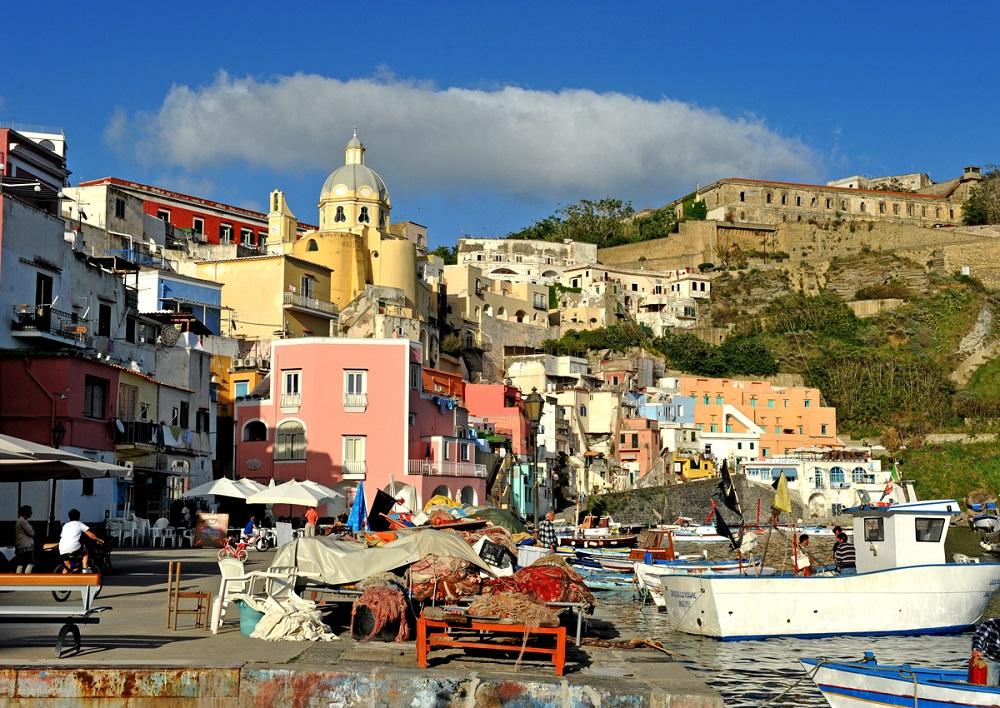 la foto a colori mostra Marina Corricella dell'isola di Procida, con casette rosa e gialle, delle barche ormeggiate e gente seduta in un bar
