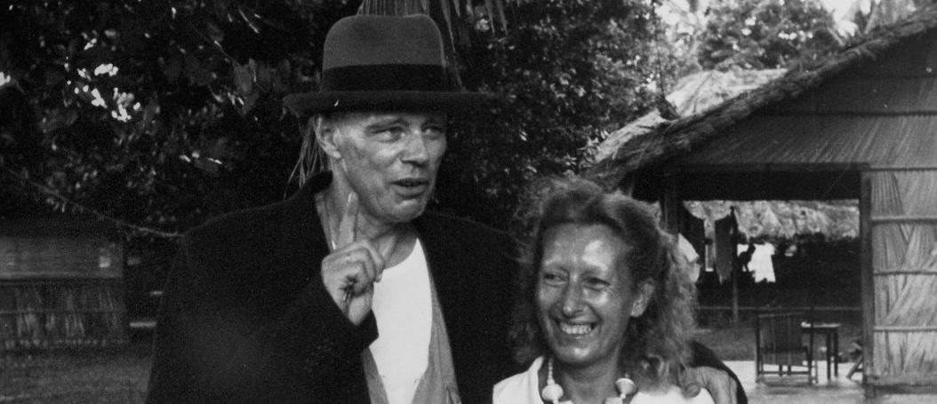 Foto in bianco e nero, un uomo con un cappello sul capo e un cappotto abbraccia amichevolmente una donna sorridente che indossa abiti chiari estivi, in un luogo esterno con molti alberi