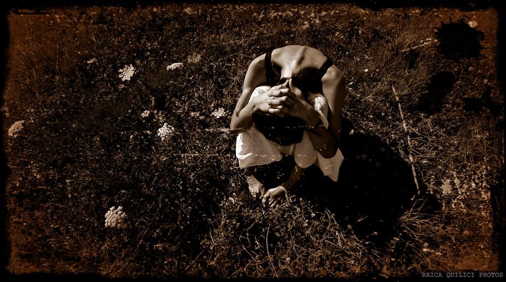 L'immagine è una foto a color seppia che mostra una donna seduta su un prato con qualche fiore qua e la. La donna è inquadrata dall'alto e tiene la testa tra le gambe e le mani sul capo, probabilmente triste o disperata