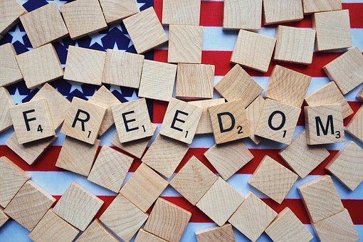"""la foto a colori mostra molte tessere quadrate di legno sparse; su sette di esse ci sono scritte, su ciascuna, le lettere che compogono la parola """"freedom"""", """"libertà""""."""