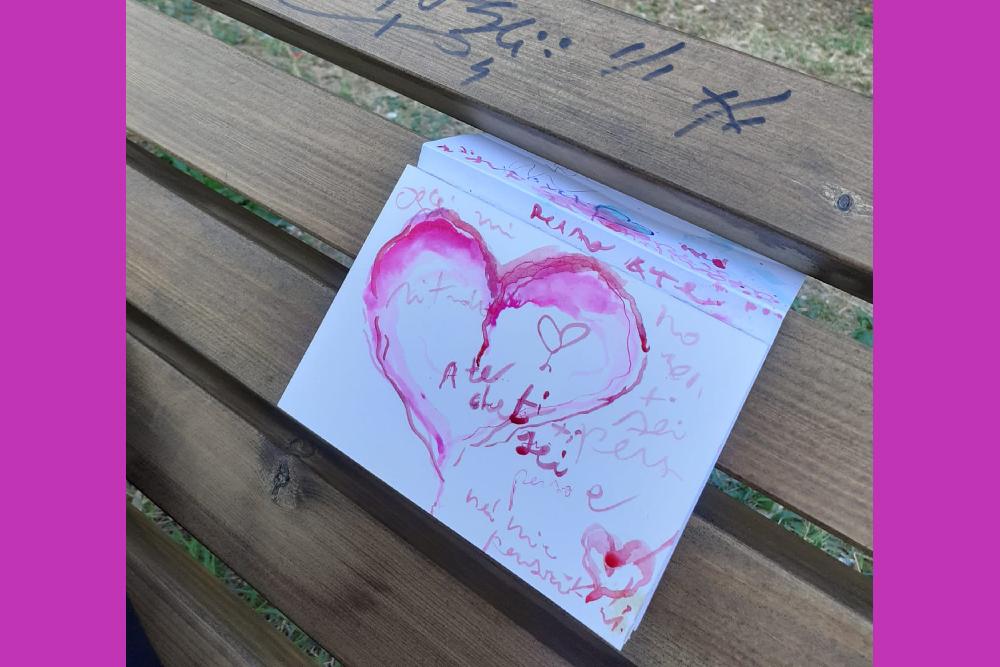 l'immagine mostra un foglio di carta piegato infilato tra le assi di legno di una panchina. Sul foglio è disegnato un cuore con acquarello rosa ed alcune scritte