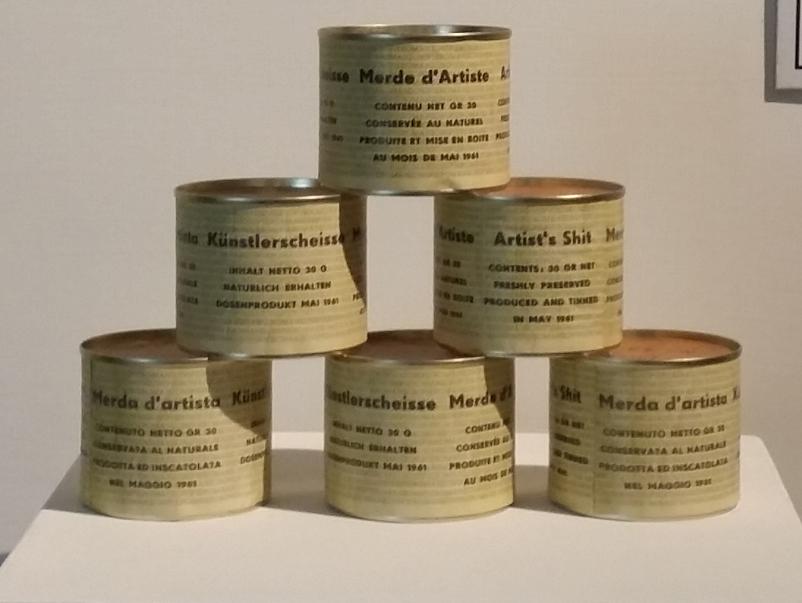 """L'immagine mostra una delle numerose versioni dell'opera di Piero Manzoni """"Merda d'Artista"""". In questa variante, le lattine (coperte di carta gialla con le scritte nere su di esse) sono impilate a formare una piramide come i prodotti esposti nella vetrina di un negozio di alimentari"""