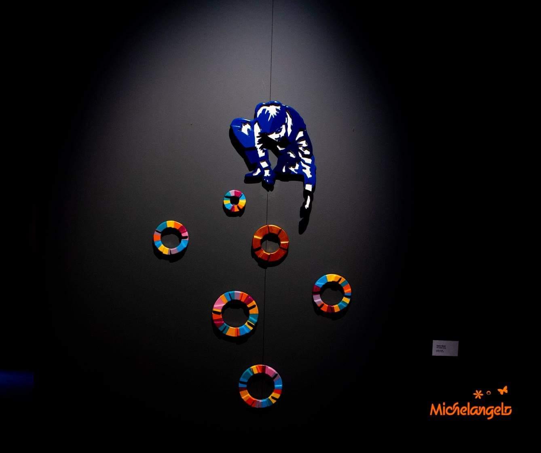 su uno sfondo nero sono disposti 5 cerchi colorati e di grandezze diverse. I cerchi sono sormontati da una immagine stilizzata di un uomo che tira su un filo da cui pendono due cerchi