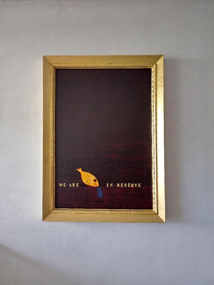 L'immagine mostra una delle opere di Beppe Sabatino appartenenti alla serie PESCIBAROCCHII. L'opera è una tela verticale rosso scuro con un pesce giallo nella parte inferiore. il pesce divide in due la frase WE ARE IN RESERVE