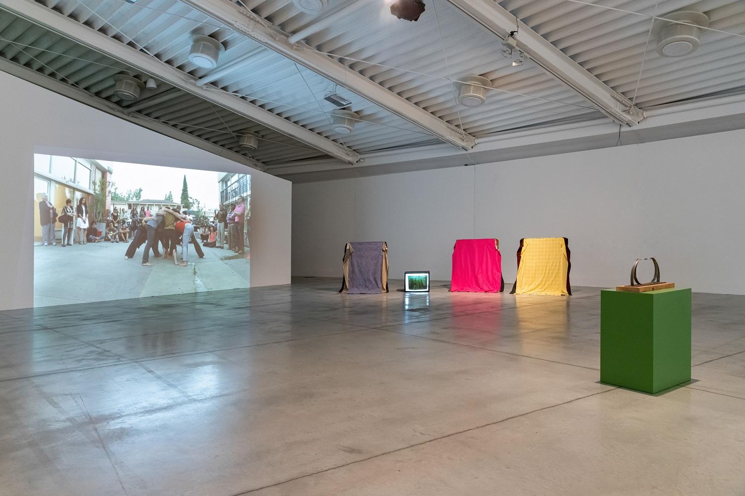 la foto a colori mostra due poltrone ricoperte rispettivamente da un telo giallo e un telo fucsia, un'opera d'arte simile ad un anello posta su un piedistallo verde chiaro e uno schermo che riproduce un'immagine di gente in lotta come nel rugby