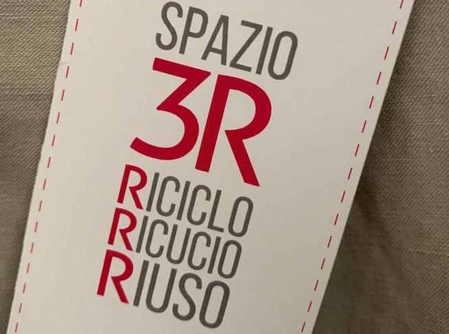 targhetta di un capo dell'Associazione Spazio3R Riciclo Ricucio Riuso, scritte in grigio e rosso su fondo chiaro