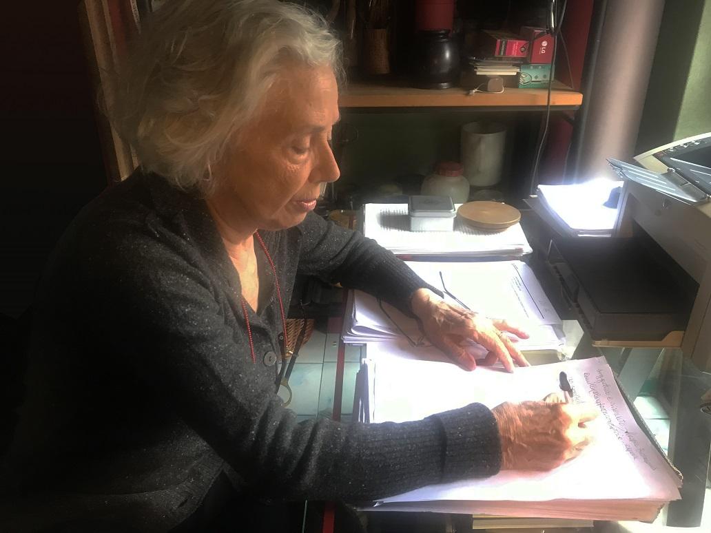 la foto a colori mostra la scrittrice Alda Mercante a scrivere su fogli di carta a mano sulla scrivania